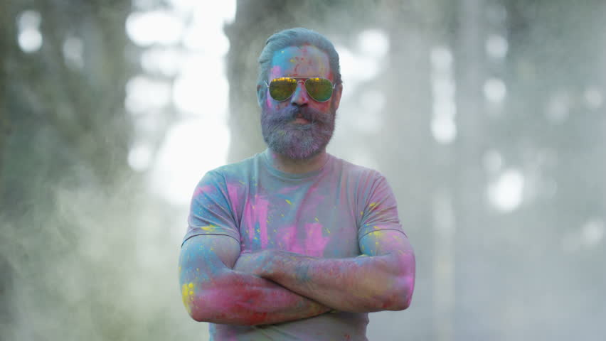 4K Portrait of serious hipster guy standing still while being covered in coloured powder at festival. Shot on RED Epic. | Shutterstock HD Video #20355010