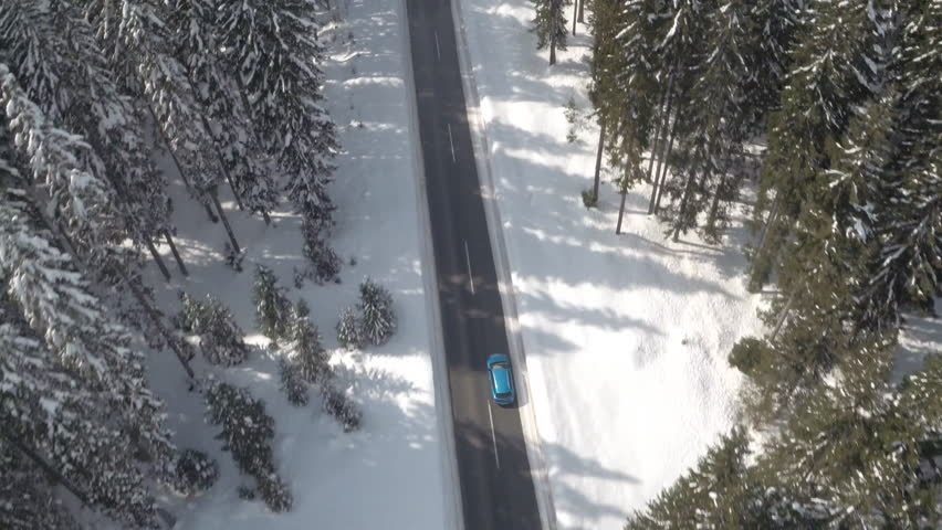 AERIAL: Flying above turquoise car driving along snowy road leading through dense evergreen mountain forest in winter. Road trip in picturesque pine tree woodland covered with fresh snow on sunny day