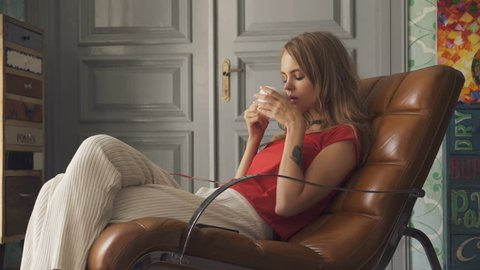 young woman with cup of tea sitting on armchair at home.