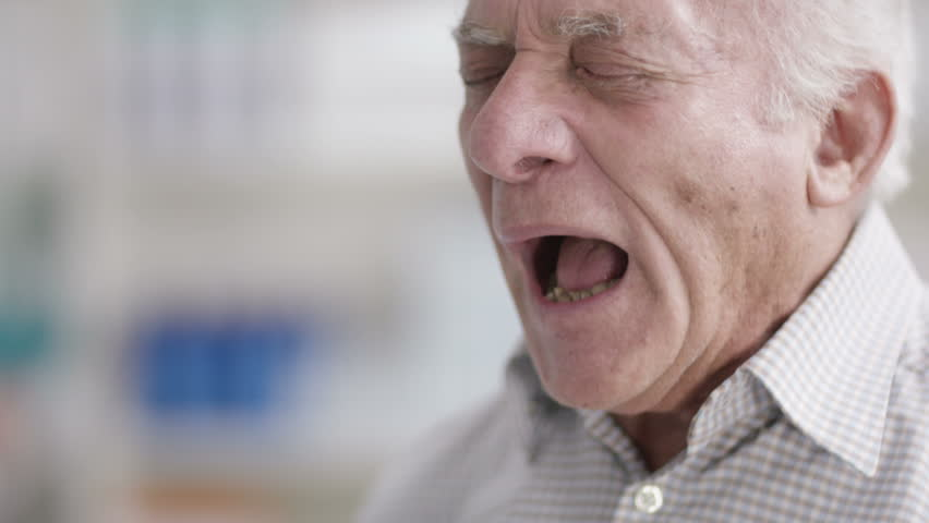 4K Close up portrait of elderly man sneezing in a chemist shop. Shot on RED Epic.