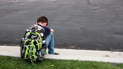A sad, lonely boy sits on a curb at school with his head on his knees.