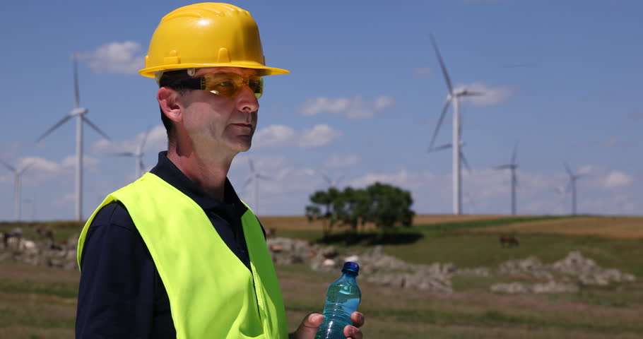 Engineer man looking at wind turbines and blueprint analyzing alternative energy worker man drinking water wind turbine power generation field ultra high definition malvernweather Images
