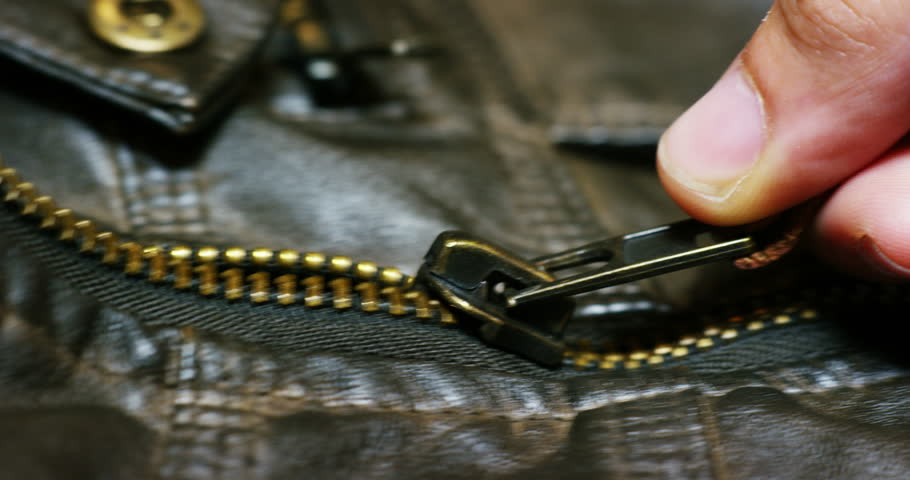 Macro shot of a zipper of a leather jacket that opens in which you see the details of the stitching and fabric texture. vintage concept, tailoring, jeans, texture, fashion