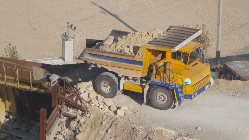 Large Dump Truck Unloads The Raw Crushed Stone Crusher