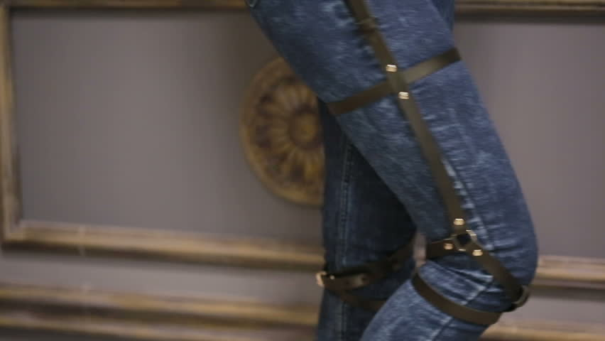 Girl in jeans with leather garter new fashion trends. straps on the hips | Shutterstock HD Video #20484700