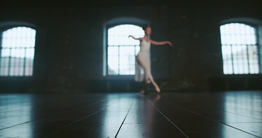 Beautiful girl dancer performs elements of classical ballet in the loft design Studio,slow motion, out of focus