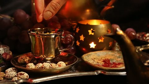Female hands with beautiful oriental accessories Making Saffron Masala milk Tea with spices. Traditional Moroccan Sweets on Tray. Gala dinner by candlelight. Arab, Turkish, Persian and Indian dishes