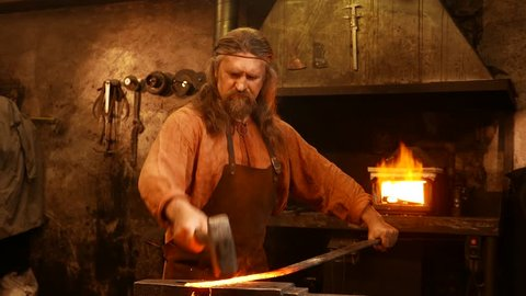 Senior blacksmith forging the molten metal on the anvil in smithy
