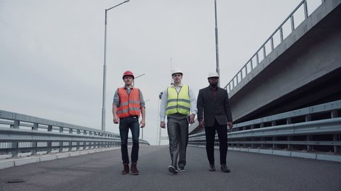 4K shot of Diverse group of three handsome male construction engineers with serious expressions walking on highway ramp. Wide angle