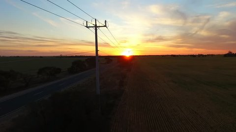 Telegraph Road. Aerial view of outback highway or open road on dusk (sunset) with semi trailer truck,   traveling on rural country high speed motorway. Telegraph poles, power lines & solitude theme.
