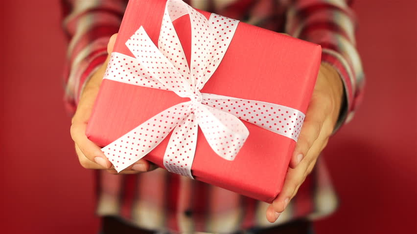 Young man gives a gift on red background red gift box with white young man gives a gift on red background red gift box with white ribbon opening congratulate happy new year merry christmas happy valentines day negle Gallery