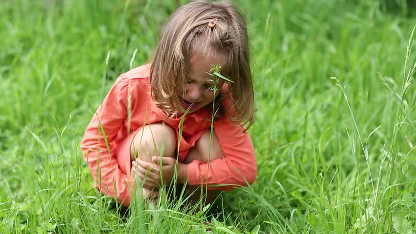 Little girl sits on green grass and crying. Girl in red dress crying, because she got burnt with nettle. True sincere weeping and emotions of little girl. Real situation, pain caused by chemical burn