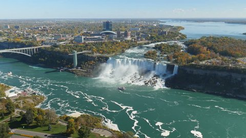 A wide aerial view of the American Falls and fall foliage on the Niagara River in Niagara Falls, New York.