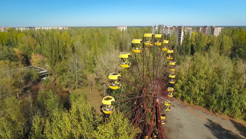 Panning orbit around abandoned ferris wheel of Pripyat Town after meltdown of Chernobyl nuclear power plant in 1986. Reactor & new sarcophagus are seen on the horizon. Oct 2016.