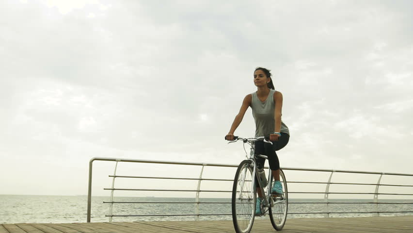 Beautiful young sexy lady riding her bycicle near the sea.