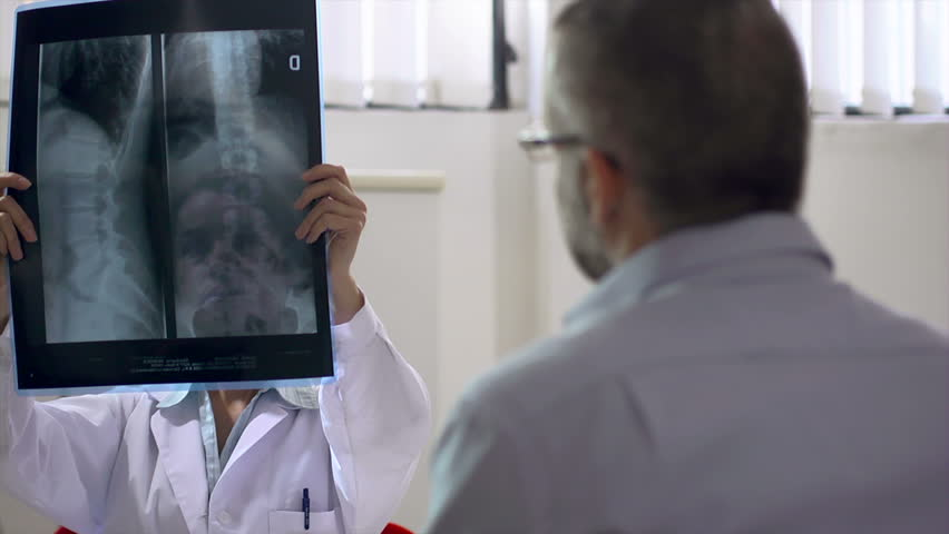 Mid adult woman at work as doctor in hospital office and talking to man after examining x-rays