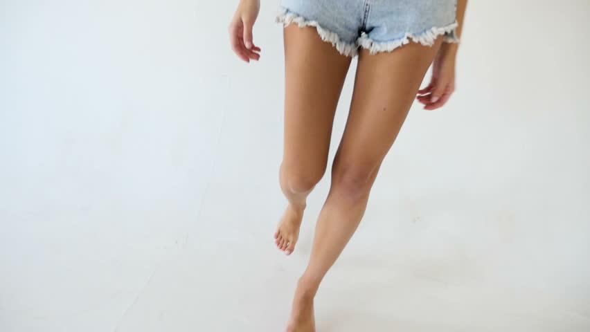 model in short denim shorts goes barefoot on the white floor