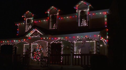 night nice two story house Christmas tree porch multicolored Christmas lights around house white lights around windows top windows small Christmas trees inside, lighted lawn art Scrooge porch right