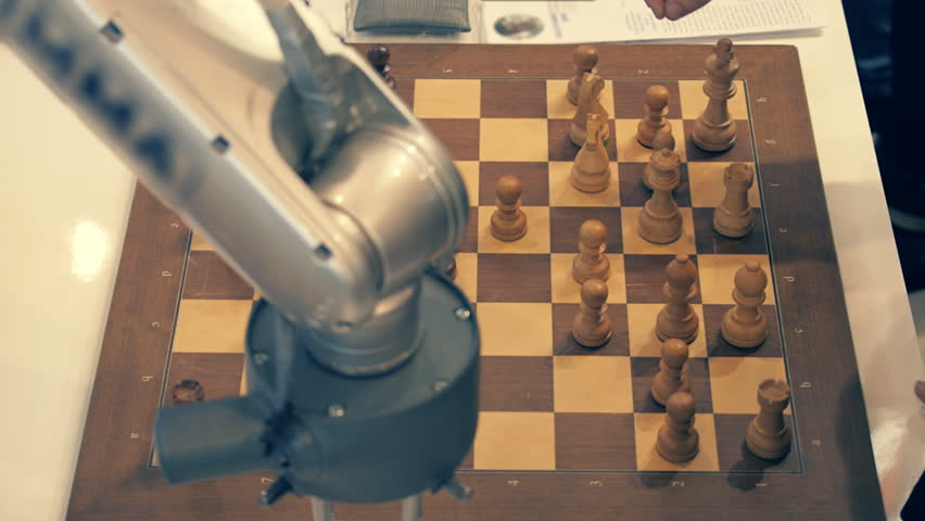 Robot playing chess with a man. Hand manipulator moves the chess and presses the key of the control watch