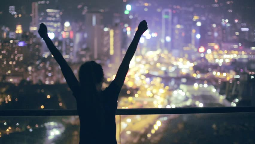 Silhouette of a young happy girl feeling awesome on the rooftop with great view over city. Success and happiness concept. Hong Kong, China.  | Shutterstock HD Video #20695510