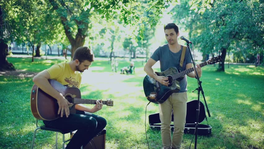 Music band. Duet. Ensemble. Singer and performer. Singer and musician. Two men play a guitar outdoors in summer park. One of the musicians singing into the microphone. Two guitars. Accompaniment.