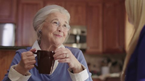 An elderly senior woman enjoys talking with a friend while drinking coffee. Shot in 4K UHD.
