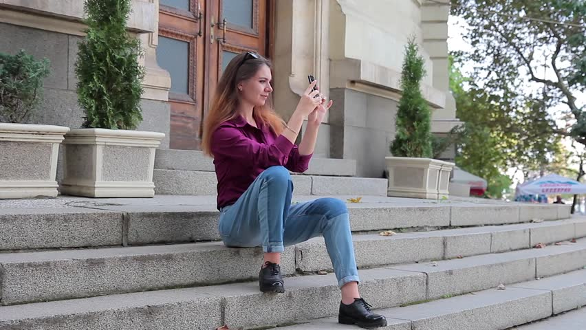 Young woman making mobile photo on the street sitting on the steps | Shutterstock HD Video #20757034