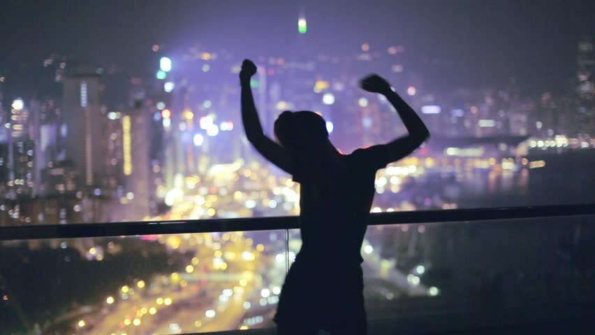 Young beautiful woman dancing on terrace during night. Young excited woman dancing on the rooftop, enjoying breathtaking view over the city at night. City lights, Party time.
