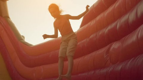 Slow Motion: Little beautiful girl jumping on an inflatable trampoline.