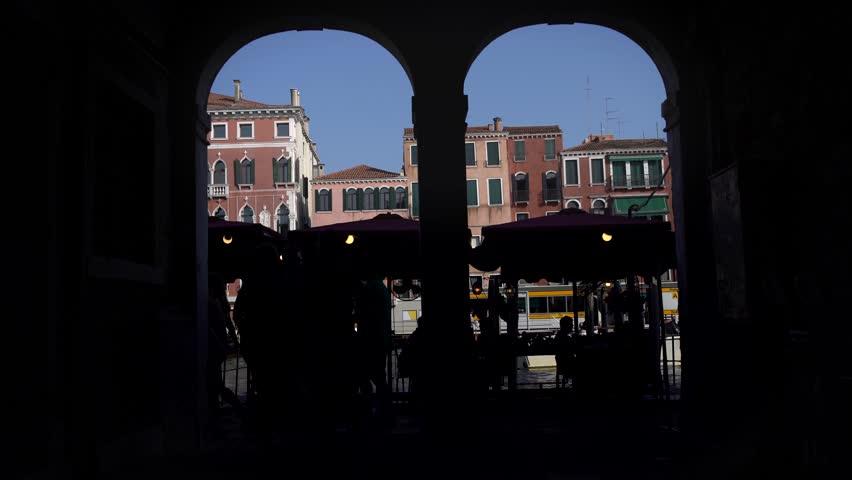 Backlit shot of tourists in open-air-market in Venezia, Venice, under ancient arches. Restaurants. | Shutterstock HD Video #20797180
