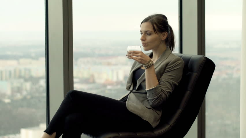 elegant woman relaxing on chair and admire view form window at