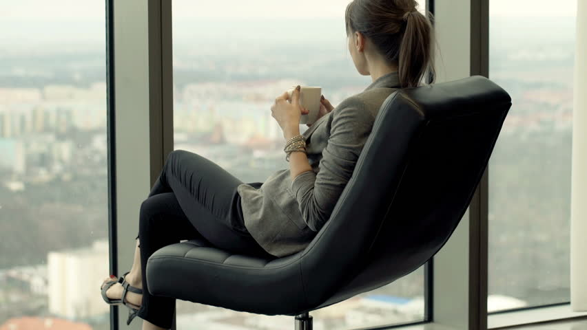 Woman drinking coffee and admire view from window while sitting on chair at home  | Shutterstock HD Video #20819866