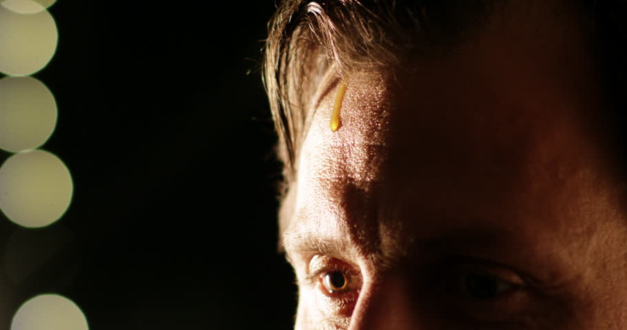 Man in focus wit a drop of sweat coming down on his forehead. Dark background with yellow bright lights. Ready for performance on stage or television. Brown eye close up on forehead. Slow motion.