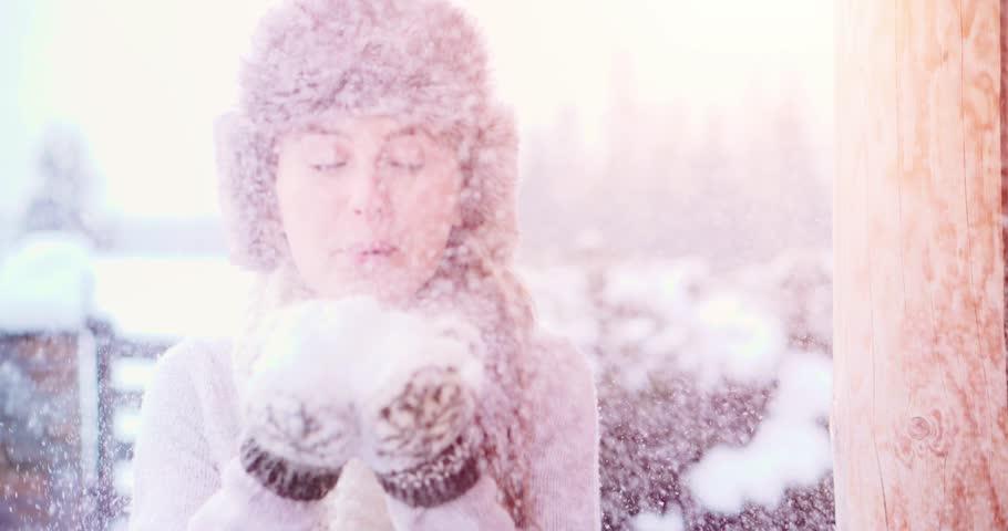 Blowing Snow, SLOW MOTION 120fps 4K DCi. Beautiful Joyful Female Model having fun near wooden log Cottage. Young woman enjoying magical snowfall. Winter wonderland. Snow Day near Mountain Chalet Cabin