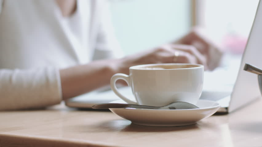 Cropped blurred female hands typing at laptop and taking drink from coffee cup near her. | Shutterstock HD Video #20850160