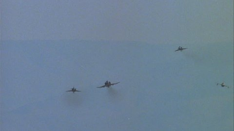 day Ground air F 4E Phantom II followed F 16 Falcon two MiG 23s F 21 Kfirs, fighter jets, flying close together they fly over warfare, dogfight playback