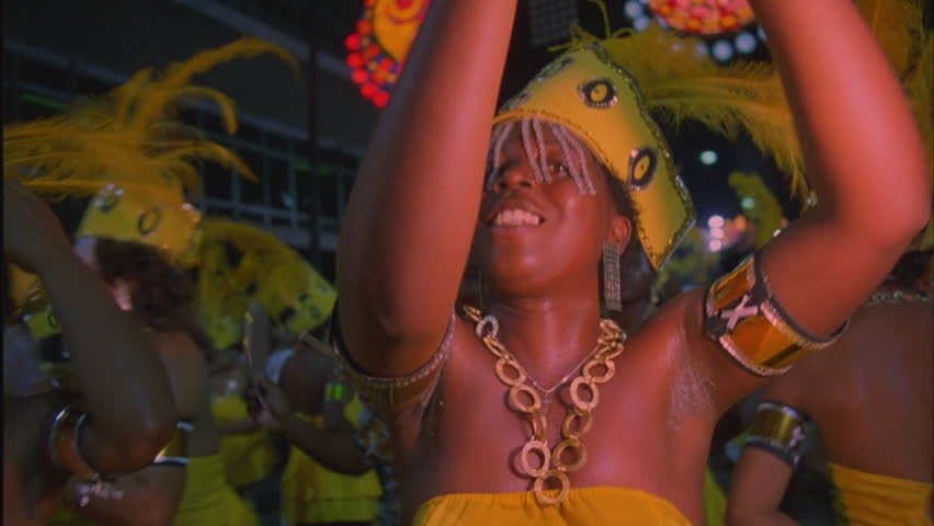 night Handheld SPOV Tilt down up over dancing woman yellow costume with headdress, group other dancers matching costumes Rio de Janeiro, Carnival