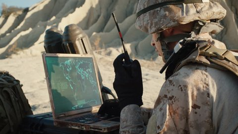 Soldier is Using Laptop Computer for Tracking the Target and Radio for Communication During Military Operation in the Desert. Shot on RED EPIC Cinema Camera in 4K (UHD).