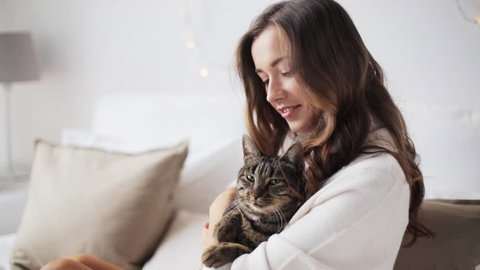 pets and people concept - happy young woman with cat in bed at home