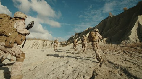 Follow Shot of Squad of Soldiers Running Forward During Military Operation in the Desert. Slow motion. Shot on RED EPIC Cinema Camera in 4K (UHD).