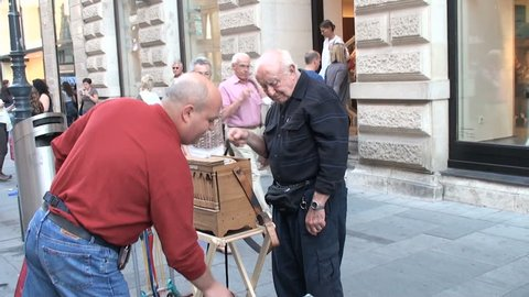 VIENNA, AUSTRIA – SEPTEMBER  20, 2011:  People give money to elderly man who plays the street organ in the central street of Vienna