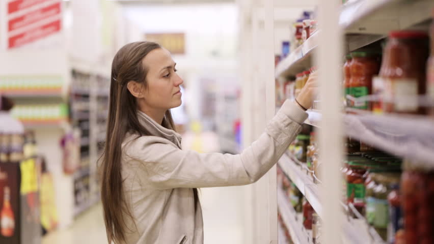 Young woman is choosing sauce in the supermarket. Woman take a bottle, reading and put to the red shopping basket. No visible trademarks or logos in scene. | Shutterstock HD Video #20904700