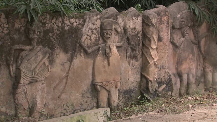 Osogbo, Nigeria - August 2013; CU carved figures in wall of Sacred Grove, motorbike passes by.