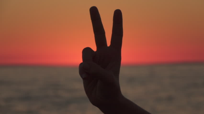 SLOW MOTION, CLOSE UP, DOF: Showing a victory hand gesture, raising and parting index and middle fingers, while the other fingers are clenched. Peace sign with magical peachy sky and sea in background