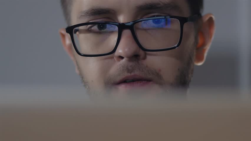 Man in black rim glasses using his computer in office. Businessman with Screen reflection in the lens | Shutterstock HD Video #20936830