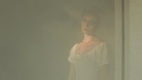 VIRGINIA - SUMMER 2016 - Reenactment, Recreation -- Ghostly, undead woman in smoky room in haunted house.  Paranormal, poltergeist.  Mystery woman with pale pallor, 19th century clothing in dank room