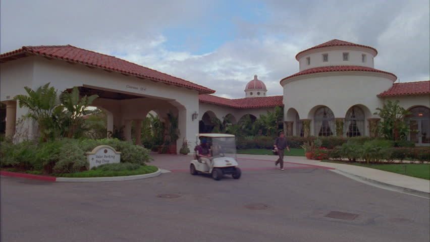 Day Hold ND golf country club stucco, tiled roof, Spanish style rotunda room arched windows, palms see person with clubs followed golf cart