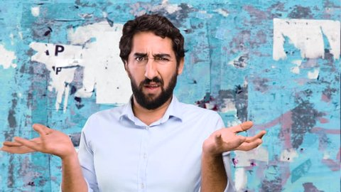 young funny man confused on grunge wall