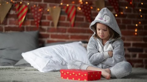 Cute little girl is unhappy with her Christmas gift by a fireplace in a her bed on Xmas morning