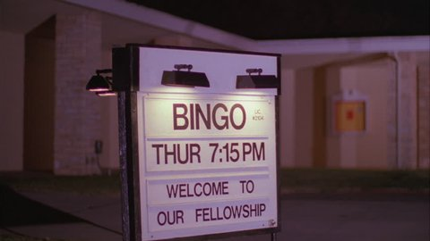night Tight Rack focus Bingo Fellowship Welcome sign just doors Midwest church school auditorium, light brick red accents
